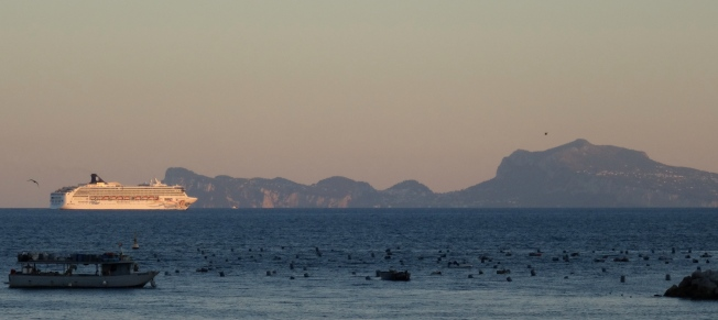 A cruise ship heads out of the Bay of Naples past the island of Capri.