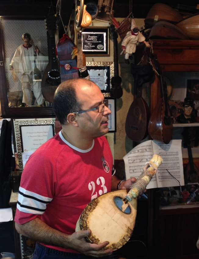 Luthier Salvatore Masiello explaining the making of the mandolin to the crowd in his tiny 'bottega' in Naples, Italy