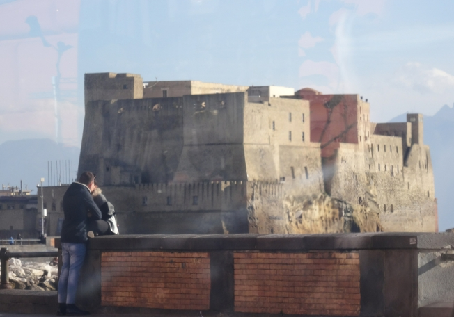 Castel dell'Ovo, seen through glass, frames the moment in Naples, Italy