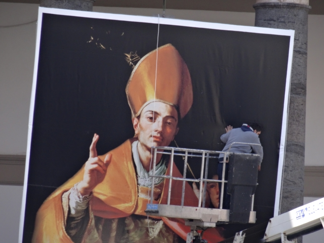 A large poster of San Gennaro is raised in Piazza cel Plebiscito for the Pope's visit in March 2015