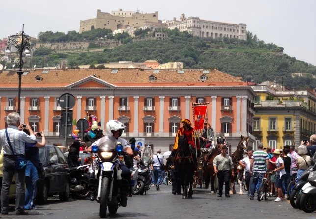 The parade of carriages leaves Piazza del Plebiscito in Naples, Italy, beneath the watchful Castel Sant'Elmo and the Certosa di San Martino