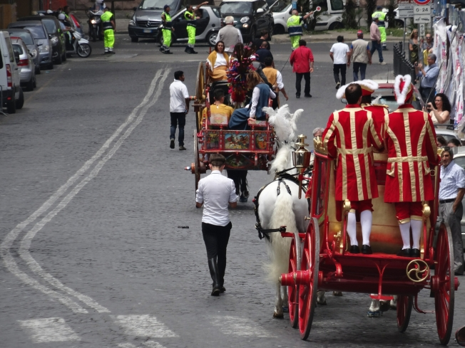 The carriages make their way back through the traffic in Naples, Italy