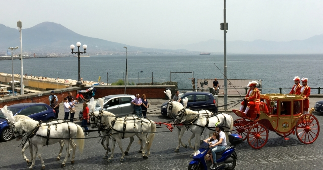 The carriages make their way along the seafront of Naples, Italy