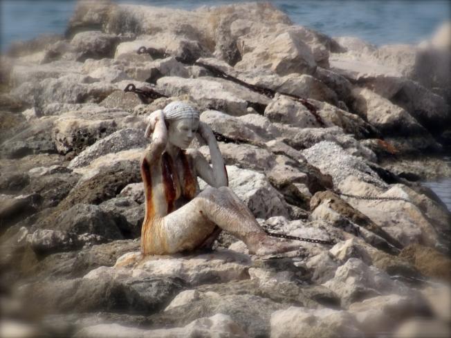 A siren on the rocks in Taranto, in Puglia, Italy